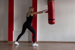 O louro atlético da jovem mulher em um t-shirt preto em caneleiras pretas dos esportes nas sapatilhas em luvas de encaixotamento  imagem de stock royalty free