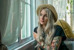 O louro bonito com vistas sonhadoras senta-se na janela e olha-se fora imagem da menina moderna Modelo da tatuagem closeup Imagens de Stock Royalty Free