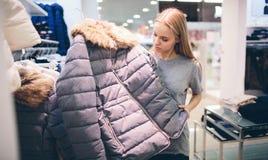 O louro bonito compra coisas novas em uma loja de roupa O vendedor trabalha no boutique fotografia de stock