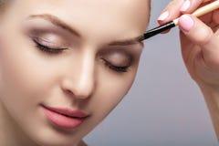 O louro bonito da mulher usa a escova profissional para a composição da sobrancelha fotografia de stock royalty free