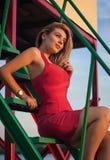 O louro bonito em um vestido vermelho 'sexy' senta-se nas etapas Fotos de Stock Royalty Free