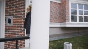 O louro bonito mostra as chaves a seus apartamentos novos em uma casa à moda do tijolo Está feliz vídeos de arquivo
