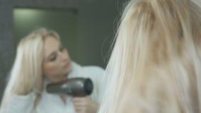 O louro bonito no roupão seca o cabelo com hairdryer filme
