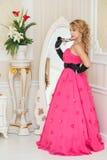 O louro bonito no vestido vermelho longo está estando ao lado do espelho Foto de Stock