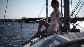 O louro bonito novo da mulher no biquinis e pareo da praia do laço senta-se na plataforma de navegar o iate filme