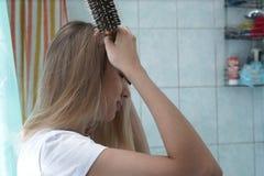 O louro bonito novo está escovando seu cabelo no banheiro imagens de stock royalty free