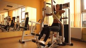 O louro bonito novo ostenta a menina que pratica em um gym em 4k