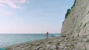 O louro caucasiano novo anda ao longo de uma praia de pedra desarrumada sob uma rocha filme