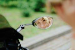 O louro da menina olha nos olhos de sorriso de um espelho da motocicleta, foco no cabelo Imagens de Stock Royalty Free