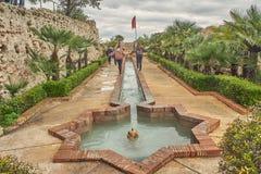 O louro dois novo e os adolescentes morenos jogam na fonte árabe dentro do castelo de Xativa em Valência, Espanha imagens de stock