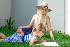 O louro e a filha da mamã estão encontrando-se na grama e estão lendo-se um livro, família feliz fotos de stock royalty free