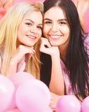 O louro e a morena nas caras de sorriso têm o divertimento no partido doméstico As meninas colocam na barriga perto dos balões, f imagem de stock royalty free