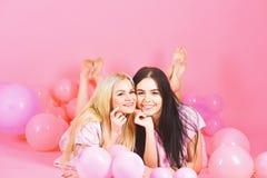 O louro e a morena nas caras de sorriso têm o divertimento no partido doméstico As meninas colocam na barriga perto dos balões, f imagens de stock