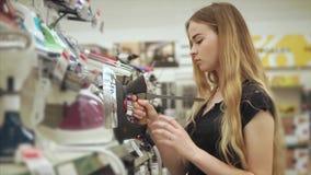 O louro está guardando à disposição uma amostra da exposição de um ferro em um supermercado vídeos de arquivo