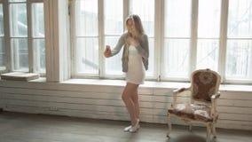 O louro feliz faz o selfie em um smartphone que está em um vestido curto Uma jovem mulher de sorriso bonita sobre contra filme