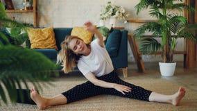 O louro flexível está fazendo esticando os exercícios em casa que sentam-se no assoalho no apartamento moderno A menina está dobr filme