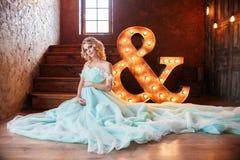 O louro grávido da noiva está preparando-se para transformar-se uma mãe e uma esposa Vestido longo de turquesa em um corpo da men Foto de Stock