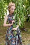 O louro macio doce bonito da menina com olhos azuis está perto de uma árvore com ramos longos com um ramo das flores em suas mãos Fotos de Stock