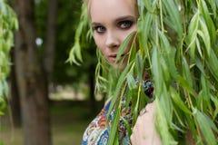 O louro macio doce bonito da menina com olhos azuis está perto de uma árvore com ramos longos com um ramo das flores em suas mãos Foto de Stock Royalty Free