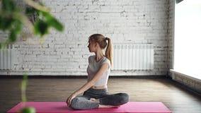 O louro magro atrativo está praticando a ioga que faz as poses da torção, dobrando-se para tomar partido então relaxando na posiç vídeos de arquivo