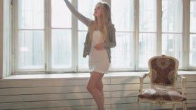 O louro na janela oposta faz um selfie em uma sala branca feita da madeira Uma jovem mulher bonita em um vestido curto video estoque