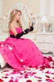 O louro no vestido vermelho longo está sentando-se na cama com rosas Fotografia de Stock Royalty Free