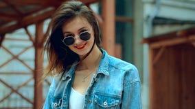 O louro novo bonito com os bordos vermelhos nos óculos de sol anda e sorri na câmera filme