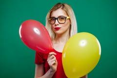 O louro que veste a parte superior vermelha curto e os vidros está dançando com os dois balões de ar em suas mãos A menina está a Fotografia de Stock Royalty Free