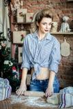 O louro 'sexy' da jovem mulher prepara a massa na cozinha dona de casa com os sacos da farinha e com o pino do rolo na cozinha imagem de stock royalty free