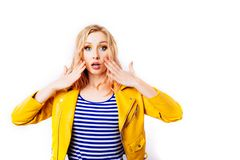 O louro surpreendido da moça em um revestimento brilhante amarelo olha o visor imagens de stock