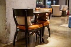 O lugar interior da arte com as cadeiras, as tabelas e os coxins internos no café urbano do vintage com cinza riscou paredes foto de stock royalty free