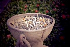 O lugar usado dos cigarros na areia no potenciômetro de pedra grande em público Imagem de Stock