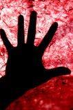 O luminoso do ser humano cede a superfície textured vermelha fotografia de stock