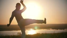 O lutador executa conluios do capoeira no monte no por do sol do verão filme