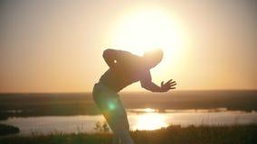 O lutador executa truques marciais com os elementos da dança no monte no por do sol do verão vídeos de arquivo