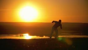 O lutador faz o truque no salto, o por do sol alaranjado sobre o rio, lento-movimento video estoque