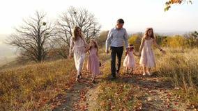 O luxo novo feliz vestiu a família que anda no parque do outono com seu cão filme