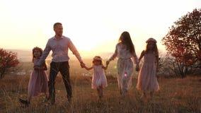 O luxo novo feliz vestiu a família que anda no parque do outono durante o por do sol filme