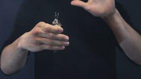 O mágico mostra um truque com uma ampola no fundo preto a ampola explode video estoque
