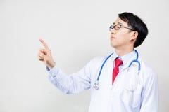 O médico asiático que usa um dedo para pressionar o tela táctil virtual no branco isolou o fundo fotografia de stock