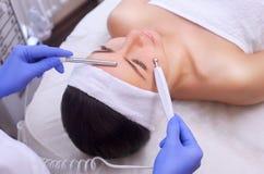 O médico-cosmetologist faz o tratamento facial bonde da pele de um bonito, jovem mulher em um salão de beleza fotografia de stock royalty free