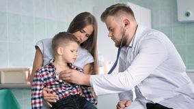 O médico no revestimento branco do laboratório examina a caixa torácica da criança doente que usa o estetoscópio video estoque