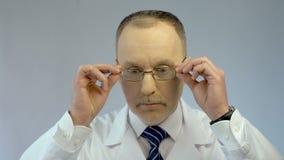 O médico principal que põe sobre vidros, apronta-se para examinar o paciente, olhando a câmera vídeos de arquivo