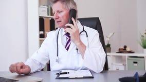 O médico que trabalha com o portátil no escritório e escreve vídeos de arquivo