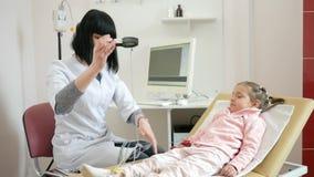 O médico recebe os pacientes, criança doente no hospital, clínica pediatra, cardiograma para crianças, cardiologista remove filme