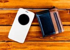 O móbil e a carteira estão na madeira imagens de stock