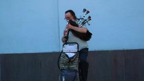 O músico da rua que joga as gaitas de fole, passadas em sentidos diferentes é pessoa vídeos de arquivo