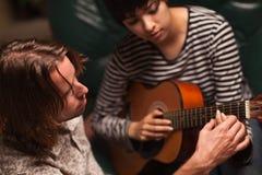 O músico ensina o estudante fêmea jogar a guitarra Fotos de Stock