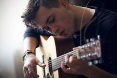 O músico executa só na guitarra acústica da seis-corda foto de stock