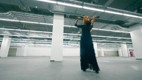 O músico fêmea joga o violino em uma sala do escritório video estoque